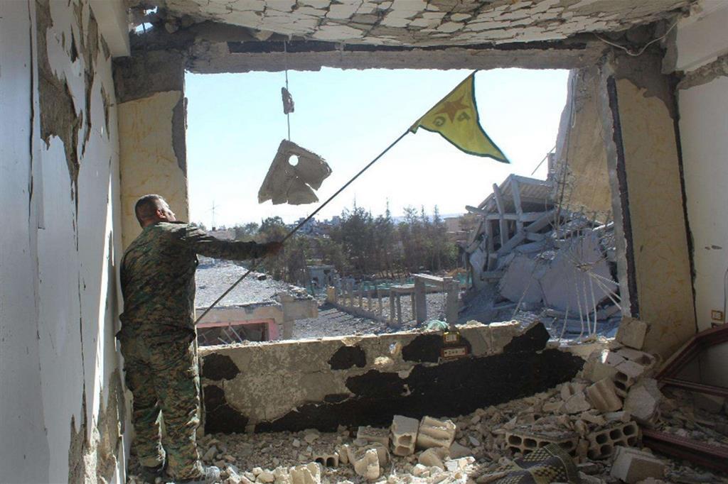 Un combattente delle Forze democratiche siriana sventola la bandiera dei peshmerga curdi a Raqqa (Ansa)