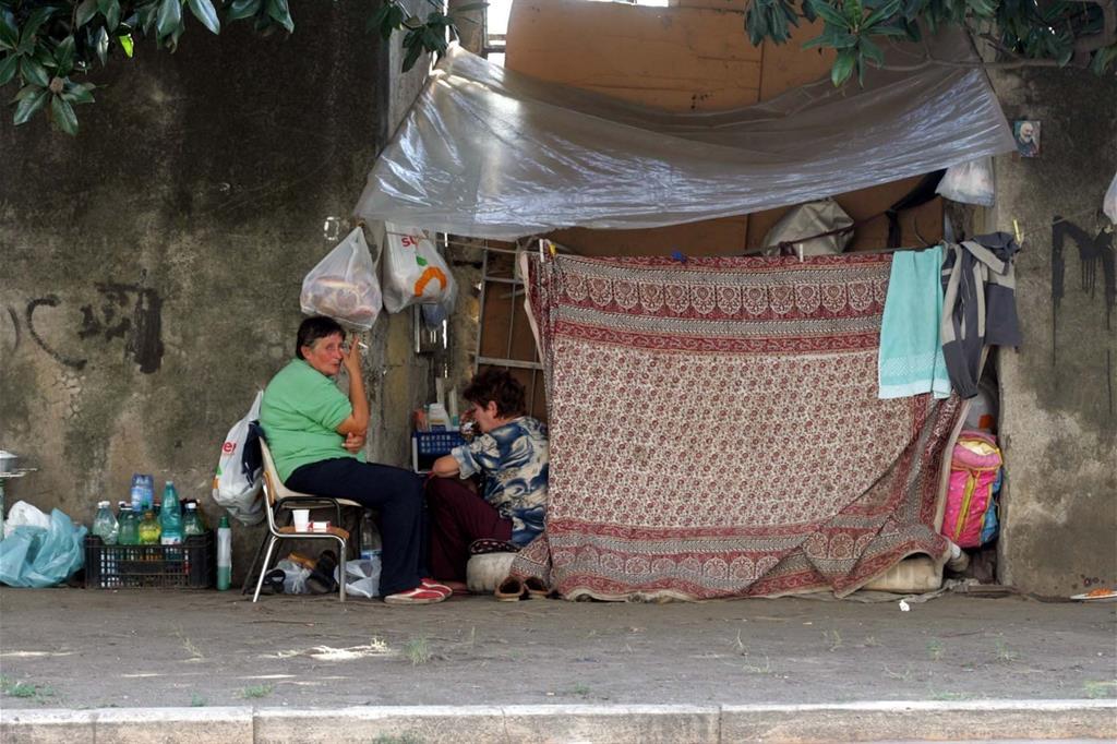 Una famiglia che abita in una baracca su un marciapiede di Napoli (Ansa)