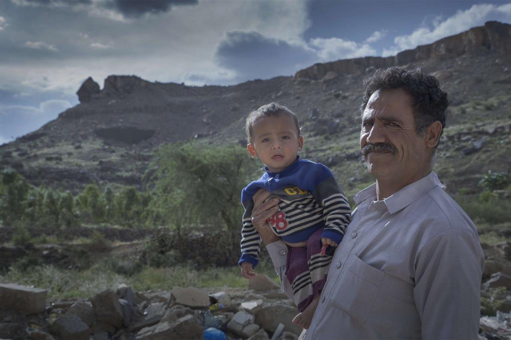 Un padre sfollato tiene il figlioletto in braccio, dargli da mangiare è un'impresa (Oxfam - Gabreez) -