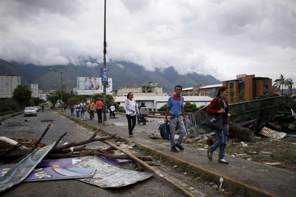 A Caracas si cammina tra i resti delle barricate (Ansa) -
