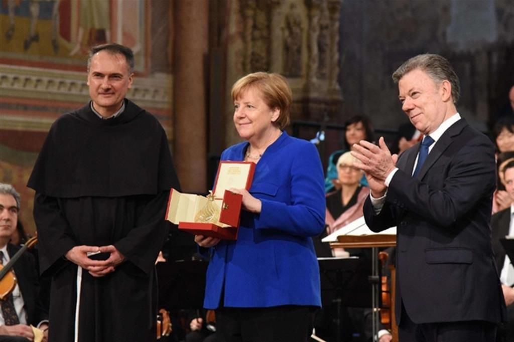 La cancelliera Angela Merkel con il presidente Juan Manuel Santos (a destra) e padre Mauro Gambetti (Ansa)
