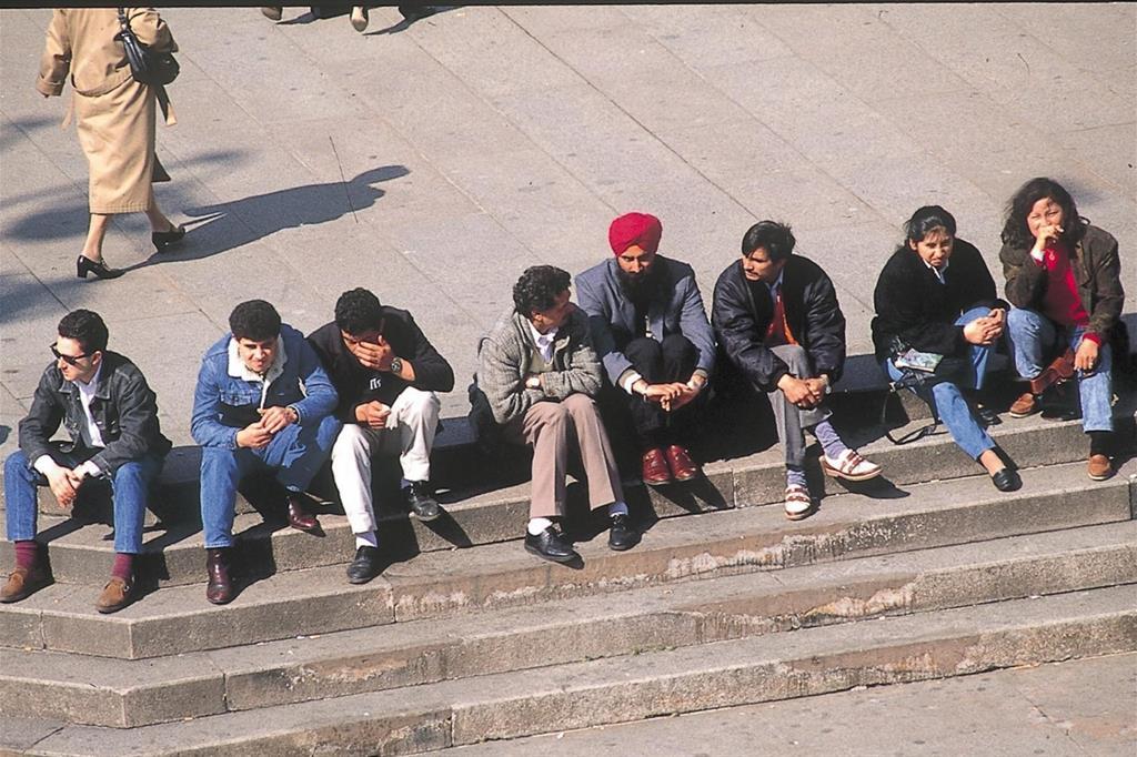 Giovani immigrati in piazza Duomo (Fotogramma)