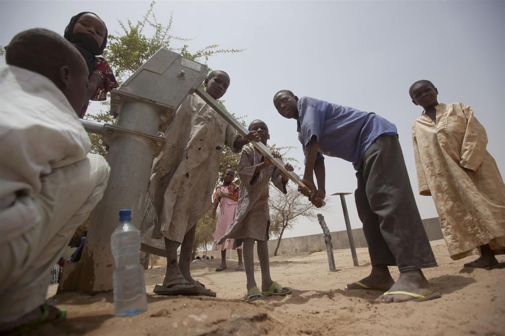 In fila per l'acqua a un pozzo alle porte di Dibinindji, villaggio nel deserto del Ciad (Ansa)