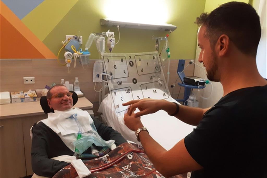 Valerio Picheca parla per suo pap�, Luigi, seguendo il movimento dei suoi occhi su una lavagna di plexiglass