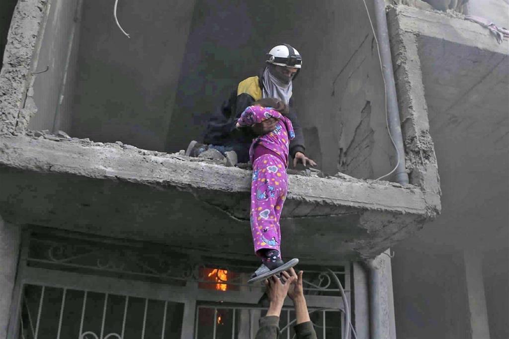 Questa foto diffusa dal gruppo White Helmets è diventato simbolo della tragedia di Ghouta: una bimba con il pigiamino rosa viene calata da un palazzo bombardato