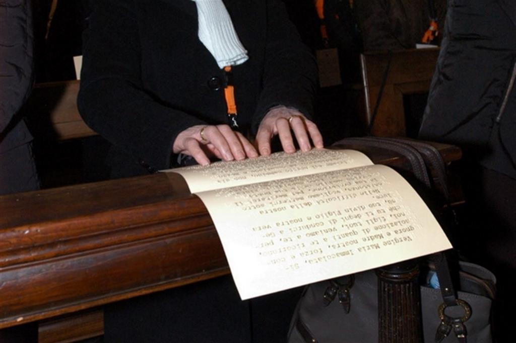 Una donna cieca legge una preghiera in Braille durante la Messa (Fotogramma)