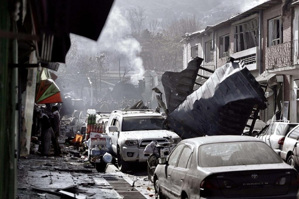 Fumo sale dalle macerie a Kabul dopo l'attentato kamikaze di sabato che ha fatto 95 vittime (Afp)