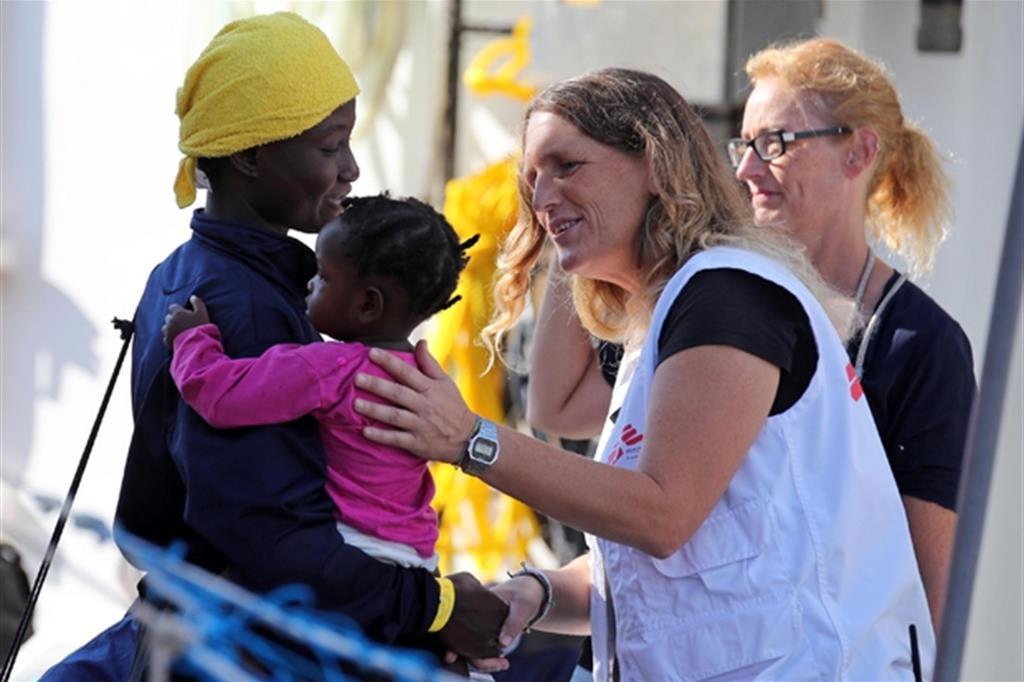 L'accoglienza di una bimba con la madre, dopo uno sbarco sulle coste italiane (Ansa)