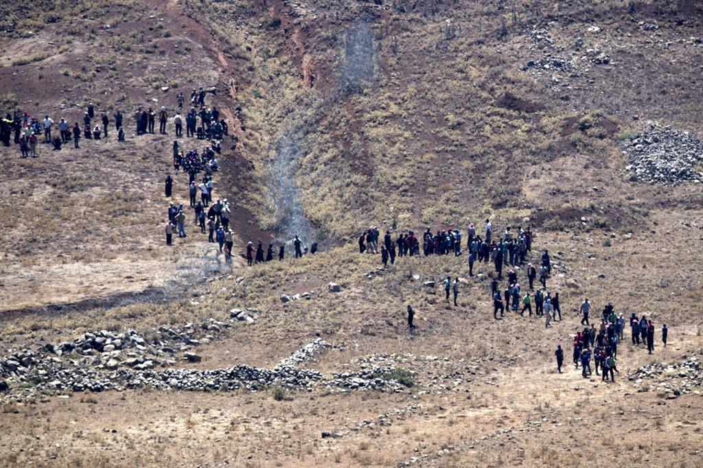 Un gruppo di siriani in fuga si avvicinano alle postazioni israeliane sulle alture del Golan chiedendo aiuto (Ansa)