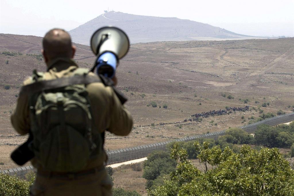 Un soldato israeliano con un altoparlante comunica con i profughi siriani. Non devono avvicinarsi troppo al muro (Ansa)