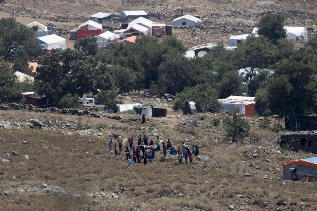 Alcuni siriani si allontano dalle casupole dove si erano rifugiati. Le bombe si avvicinani (Ansa)