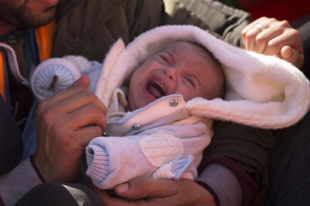 A newborn on a boat of migrants from Libya, in an archive photo (Ansa)