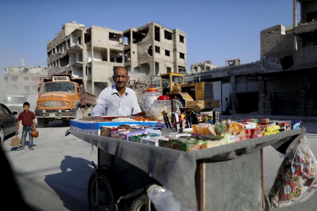 Un venditore di dolciumi a Damasco, il 15 luglio scorso: sullo sfondo un bulldozer rimuove le macerie (Ansa)