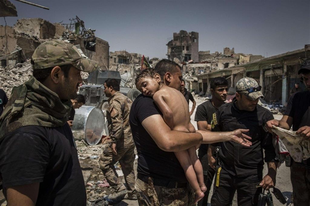 La foto è di Ivor Prickett, The New York Times. Un bambino tenuto in braccio da un soldato delle forze speciali irachene, dopo essere stato portato fuori dall'ultima area controllata dallo Stato Islamico nella città vecchia di Mosul da un uomo sospettato di essere un militante