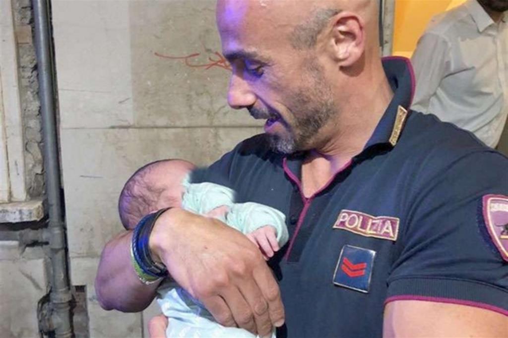 Un agente della volante con in braccio il neonato appena recuperato in vicolo Nottole, a Brescia