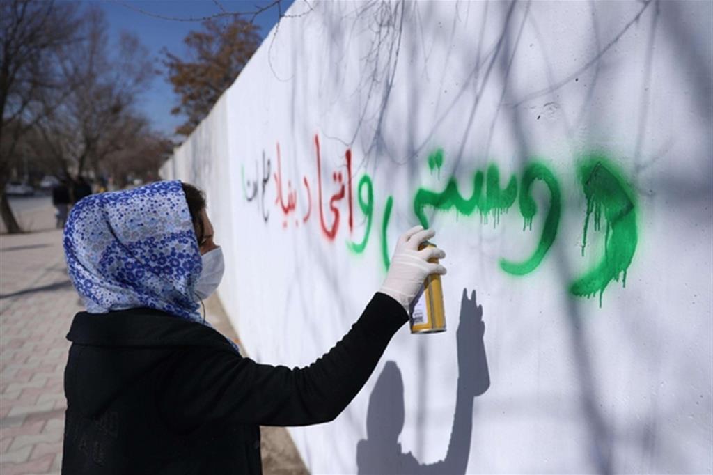 L'amicizia è la base della pace, ha scritto una donna afghana su un muro di protezione a Kabul (Ansa)