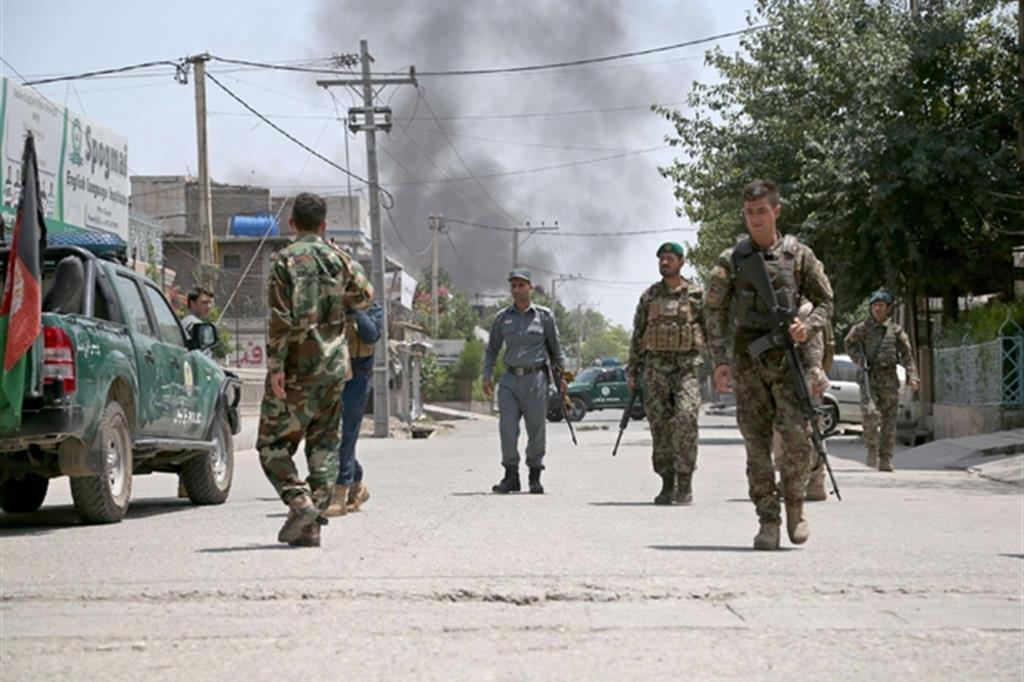 Militari afghani nella zona dell'attacco a Jalalabad: sullo sfondo il fumo dell'esplosione seguita all'attacco terroristico (Ansa)