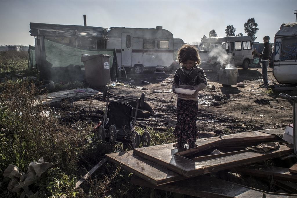 Una bambina gioca tra i rifiuti in un campo rom a Giugliano (Napoli), nella Terra dei Fuochi