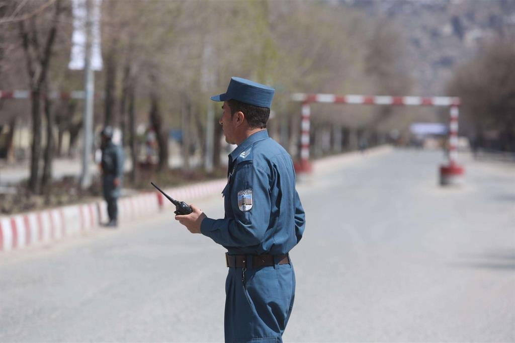 Un poliziotto vicino alla strada in cui è avvenuto l'attentato di stamane a Kabul (Ansa)
