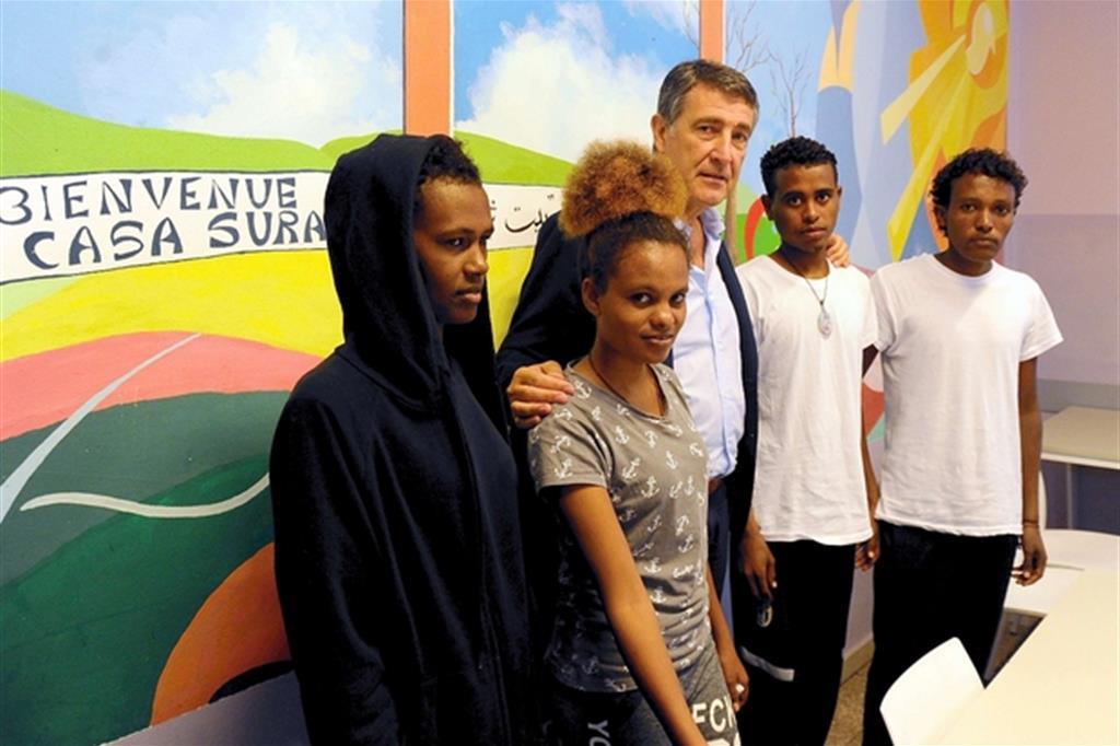 Alcuni dei migranti della nave Diciotti accolti alla Casa Suraya, con il direttore della Caritas ambrosiana Luciano Gualzetti (Fotogramma)