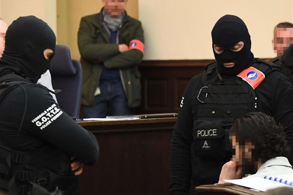 Salah Abdeslam (a destra con il volto celato perché non ha autorizzato le riprerse) in aula a Bruxelles (Ansa)