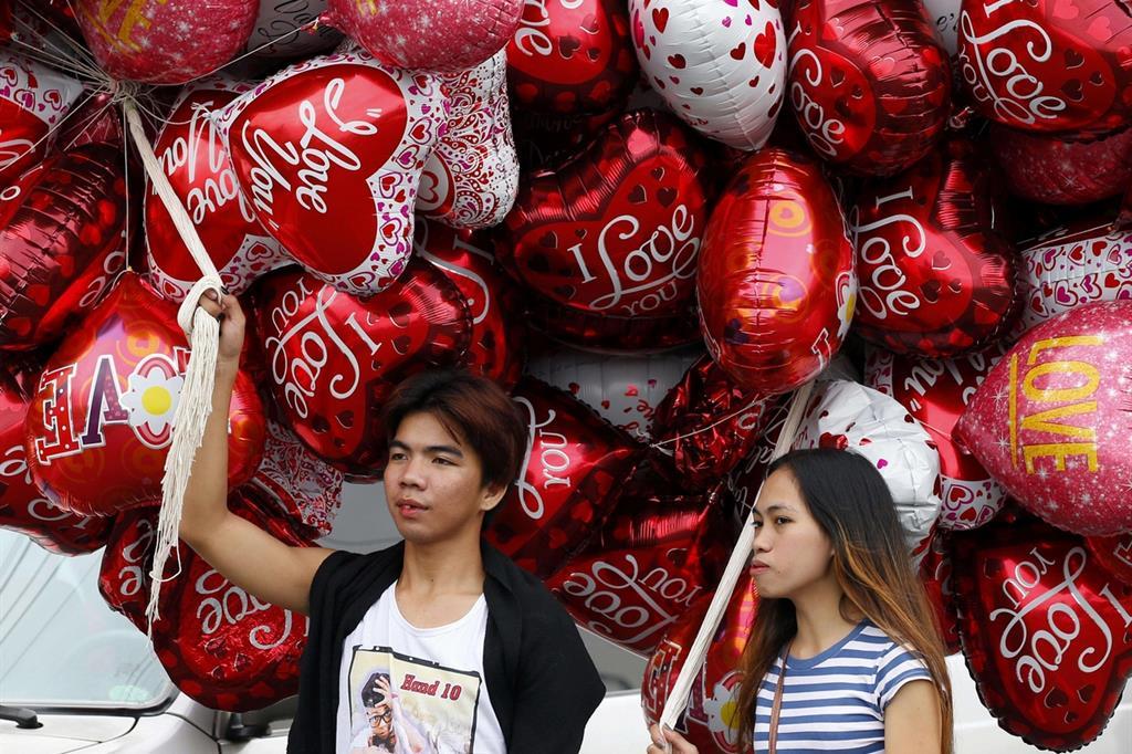 Venditori di palloncini a forma di cuore per le strade di Manila, nelle Filippine, dove San Valentino è molto festeggiato (Ansa)