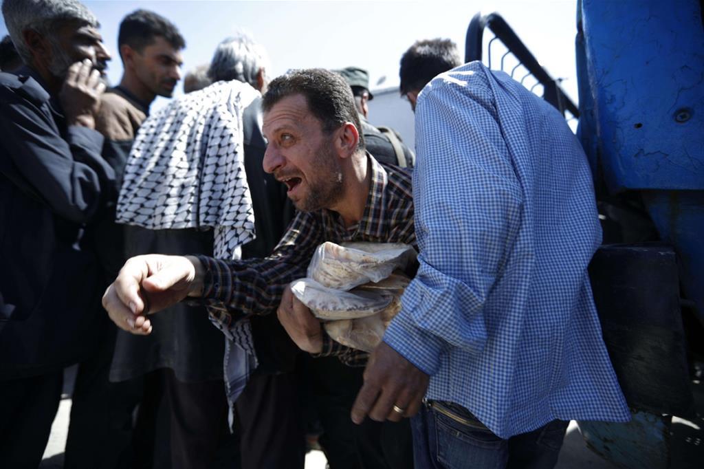 Un uomo stringe a sé il sacchetto di pane arabo appena ricevuto dalle autorità siriane a Douma, vicino a Damasco, riconquistata dall'esercito siriano dopo il sospetto attacco con i gas (Ansa) -