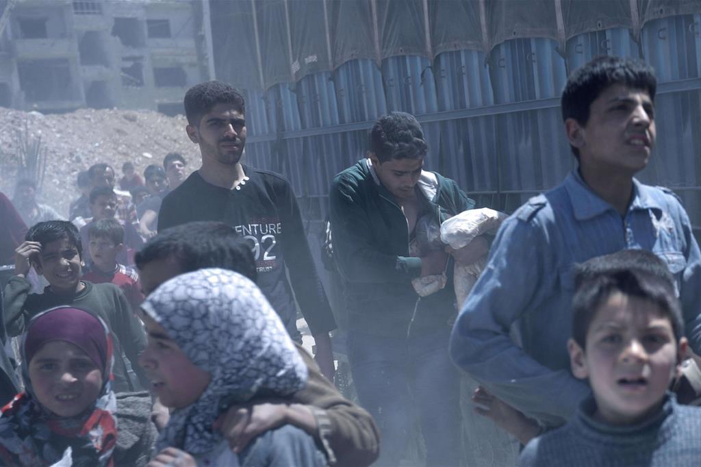 In fila anche bambini. Un ragazzo siriano nasconde sotto il giubbotto il sacchetto del pane appena ricevuto (Ansa) -