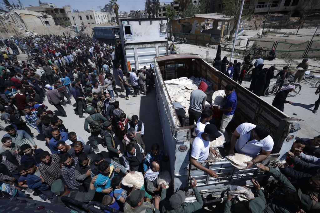 Le autorità siriane distribuiscono pane, verdura e pasta ai cittadini di Douma (Ansa) -