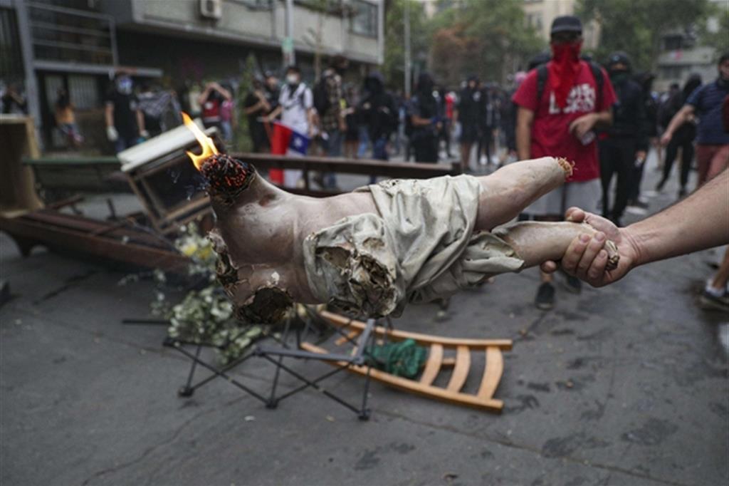 Una statua di Gesù bruciata dai manifestanti in strada a Santiago del Cile (Ansa/Ap)