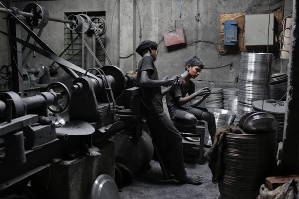 Bambini in una officina meccanica di Dacca, in Bangladesh (Ansa/Ap)