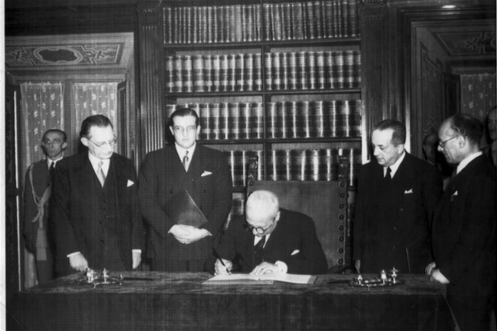 Enrico De Nicola firma la Costituzione Italiana il 27 dicembre 1947. Alla sua destra Alcide De Gasperi, a sinistra Umberto Terracini