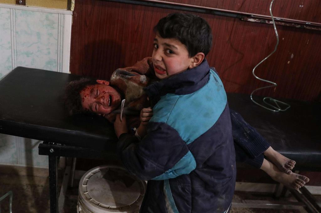 Una delle immagini di «Syria, No Exit», secondo premio nella sezione «Spot News, storie»: appena arrivati in ospedale, un bambino conforta il fratello rimasto ferito nei bombardamenti di Douma, Ghouta orientale in Siria, l'8 febbraio 2018 (Ansa)