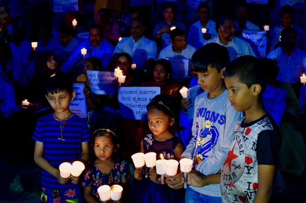 Bambini in preghiera a Bangalore, in India, per le vittime della strage di Pasqua in Sri Lanka (Ansa)