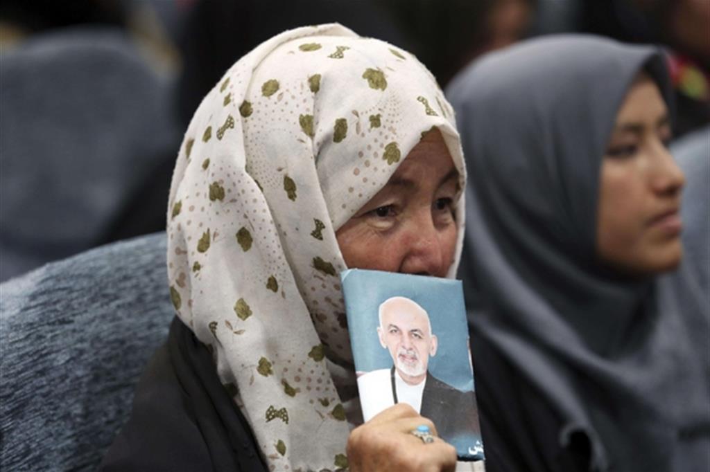 Una manifestante,a Kabul, mostra un'immagine del candidato per le presidenziali Ashraf Ghani (Ansa)