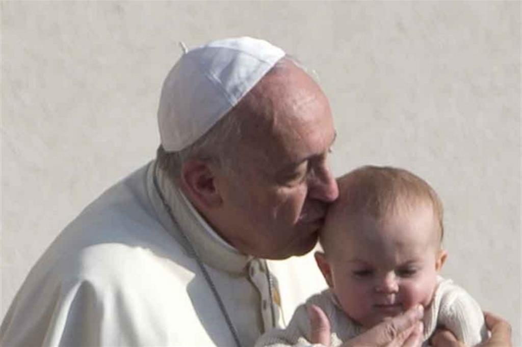 Il Papa bacia un bimbo all'udienza generale dell'8 ottobre 2014 (archivio Ap)