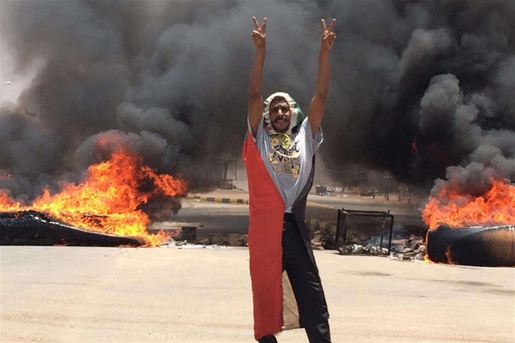 Manifestante fa segni di vittoria dopo la manifestazione fuori dal quartiere generale dell'esercito (Ansa)