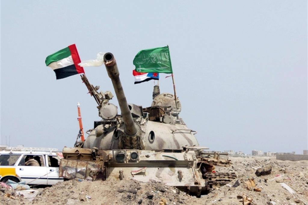 Ragazzo raccoglie bottiglie vuote a Sanaa. Sopra, un tank con le insegne saudite ed emiratine (Foto: Ansa)
