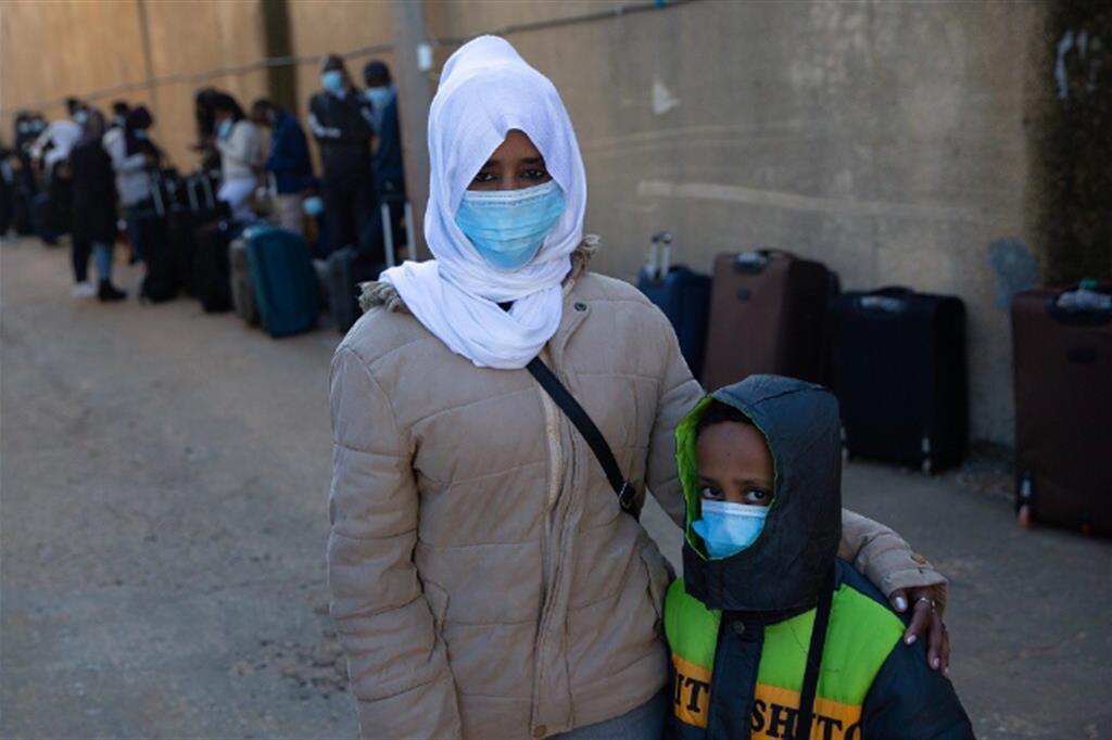 Una donna con il suo bambino in attesa del trasferimento aereo per il ricollocamento in Rwanda