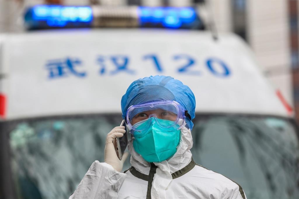 Un'infermiera parla al telefono di fronte alla sua ambulanza a Wuhan. Era il 23 gennaio