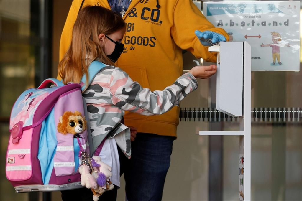 Una bambina si igienizza le mani, senza toccare il dispenser, all'ingresso della scuola - Ansa