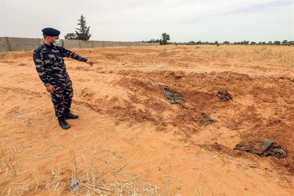 Un soldato mostra il luogo delle fosse comuni