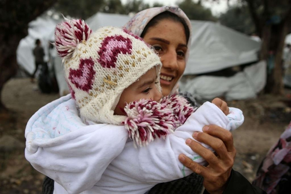 Una donna siriana con la figlia tra il fango del campo profughi di Moria sull'isola greca di Moria