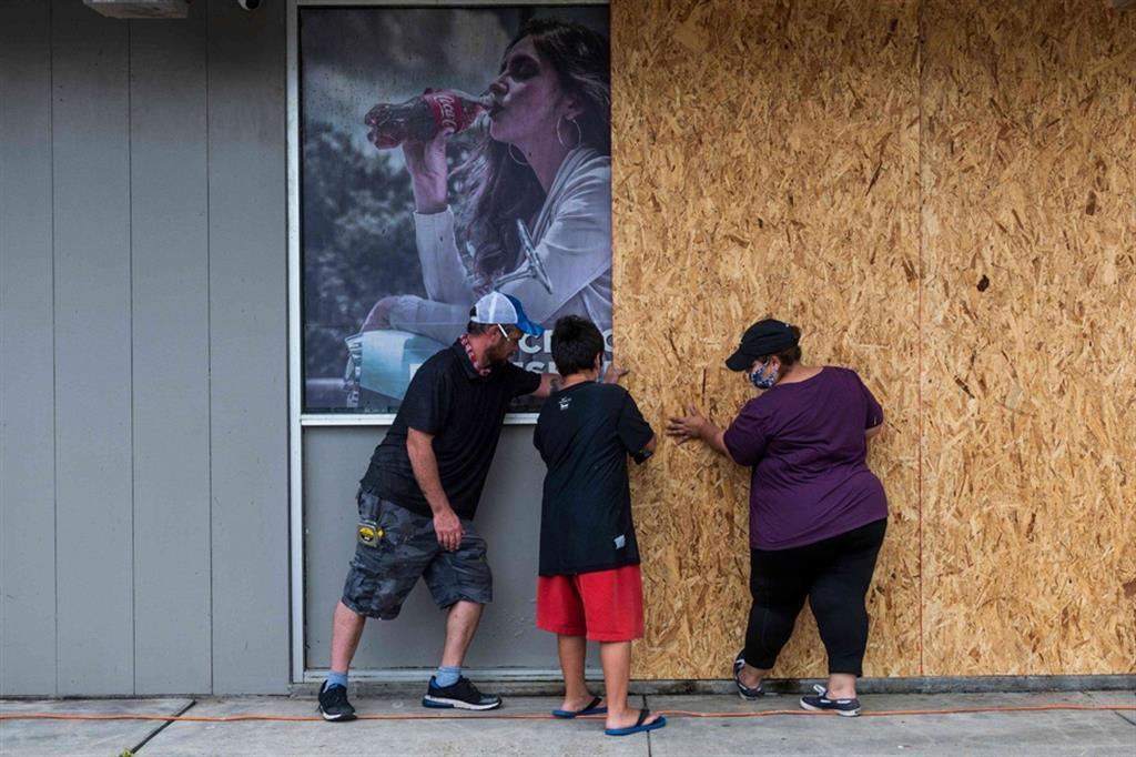 L'uragano Laura ha raggiunto le coste della Louisiana dopo essersi rafforzato a categoria 4 su una scala di 5. I proprietari di un negozio d Lake Charles, in Luoisiana, proteggono la struttura - Ansa