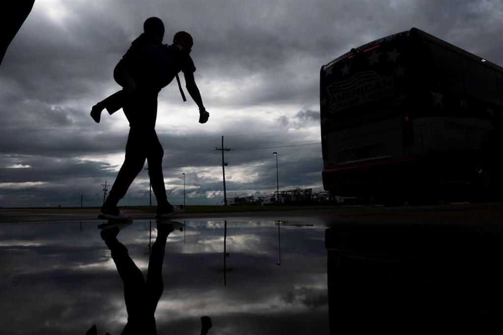 Le evacuazioni sono rese più complicate dall'emergenza Covid-19. Il governatore del Texas, Greg Abbott, ha esortato le famiglie che se lo possono permettere si trovare riparo in hotel e motel per favorire il distanziamento sociale. Qui un padre trasporta il figlio a Lake Charles, Louisiana - Ansa