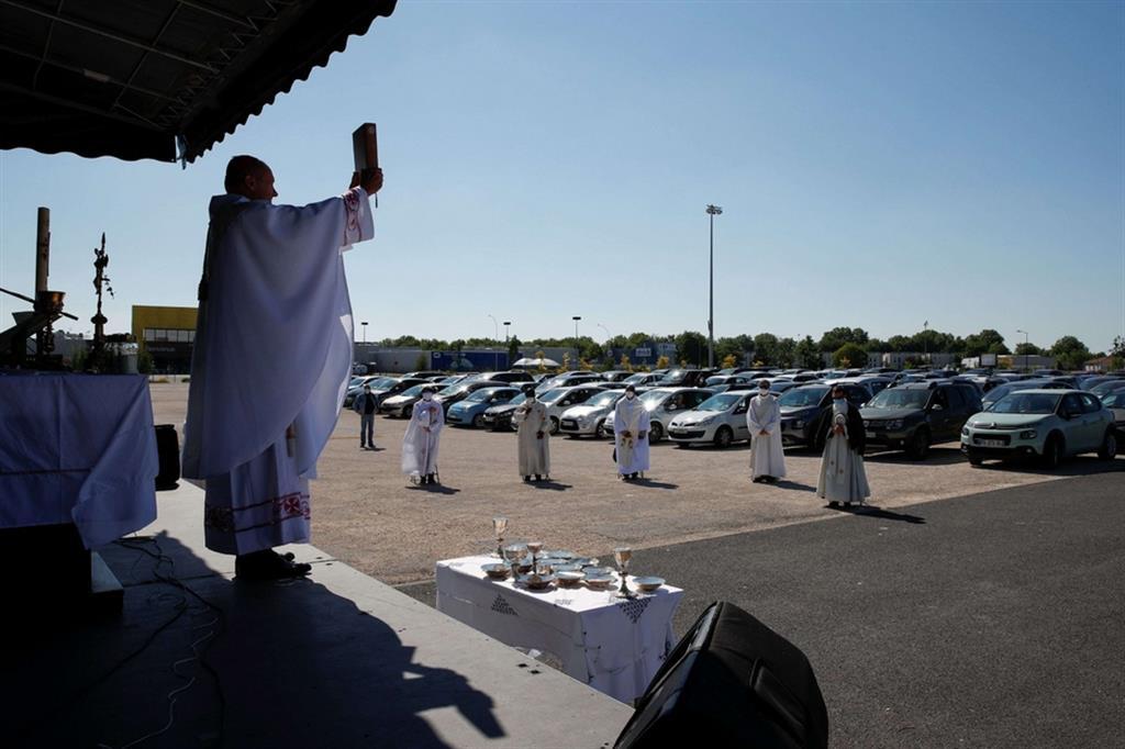 I sacerdoti hanno percorso tutte le file di auto parcheggiate per distribuire l'eucaristia, rigorosamente consegnata nelle mani dopo un passaggio con il disinfettante idroalcolico - Ansa