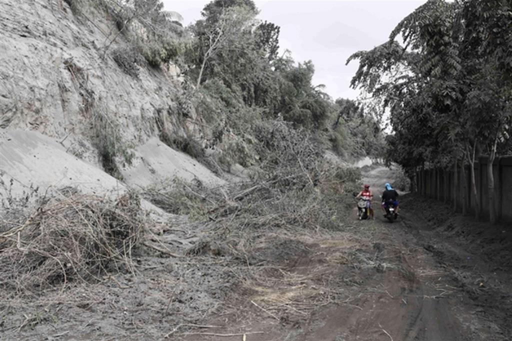 Moticiclisti in una strada coperta di cenere - Ansa