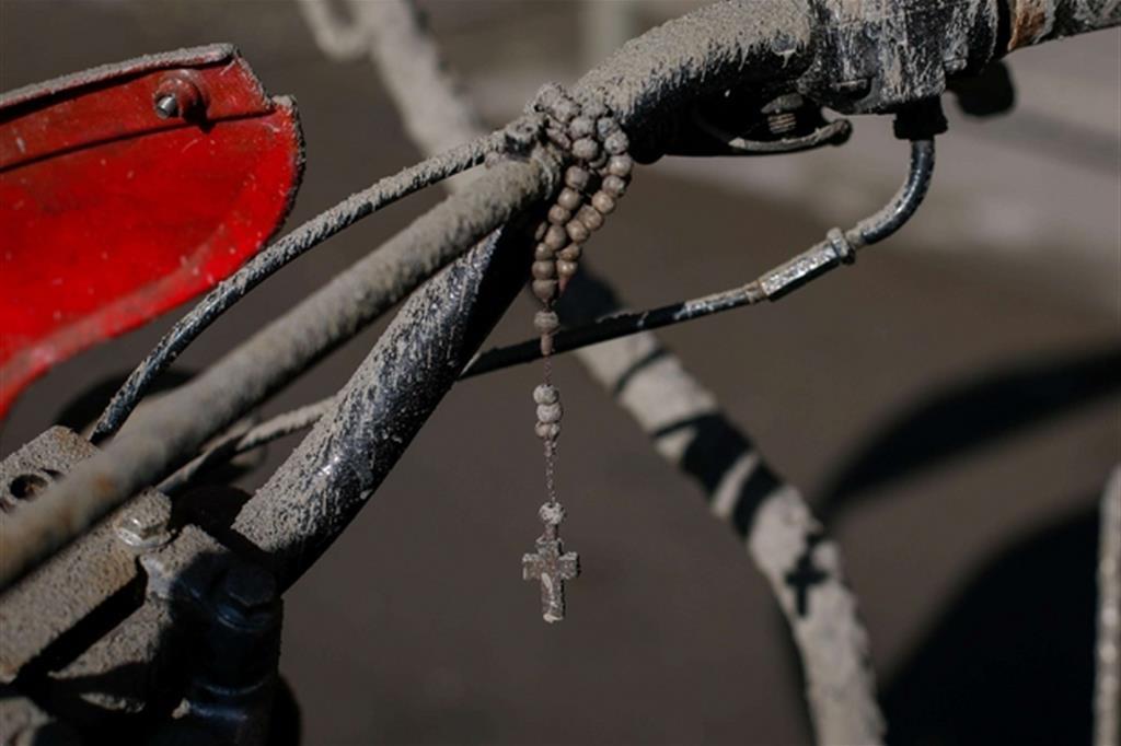 Un rosario attaccato al manubrio di un motorino ricoperto di cenere - Ansa / Mark R. Cristino