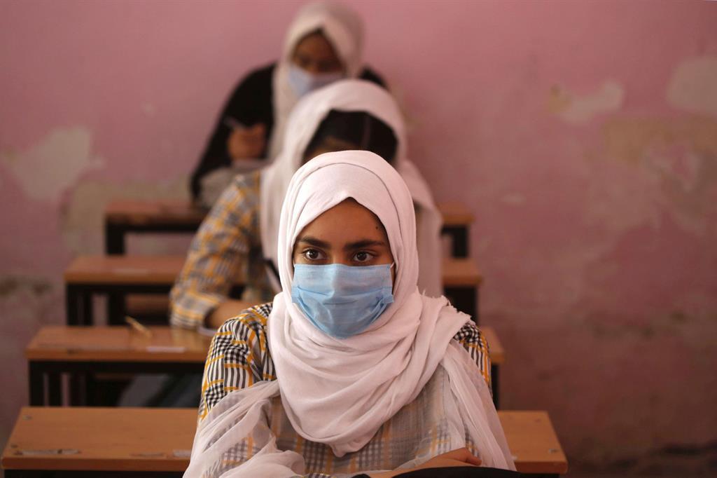 Studentesse in classe a Srinagar, nel Kashmir. Per le regole anti-Covid, solo il 50% della classe può partecipare alle lezioni in presenza - Ansa