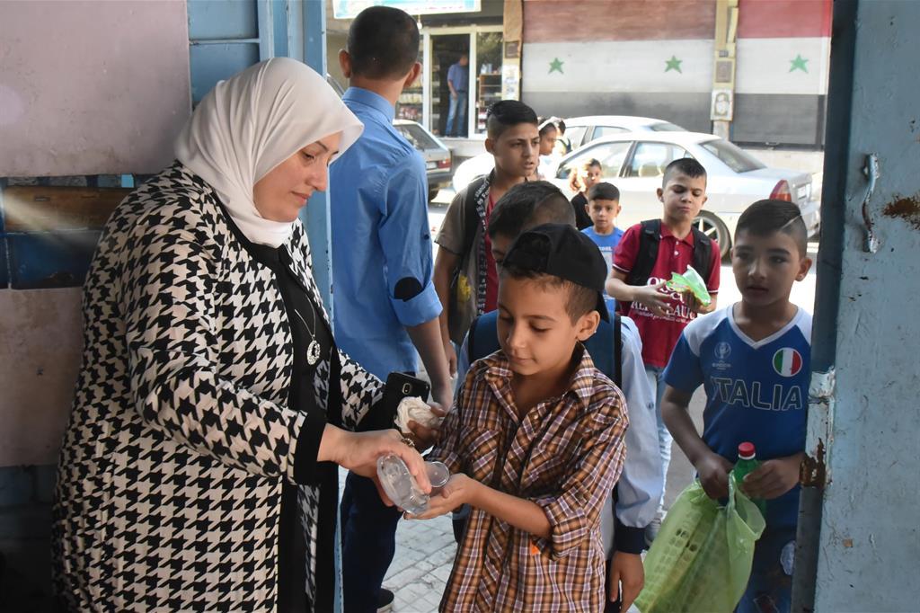 Studenti si disinfettano le mani prima di entrare in classe a Damasco, in Siria. La scuola è iniziata il 5 settembre - Ansa